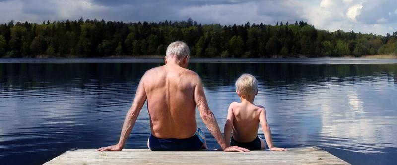 Grandfather and Grandson sitting on a footbridge